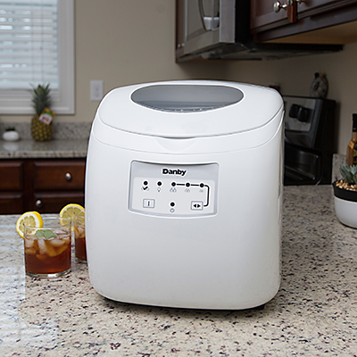 DANBY<sup>®</sup> Portable Ice Maker - This portable ice maker produces up to 25lbs of ice a day.  Self-contained water reserve container means no drain or direct plumbing required.  Features simple electronic controls with LED display and self-clean function, transparent window on lid and ice scoop.